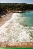 Solig strand med turister vågor tvättar stranden royaltyfri bild