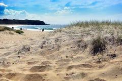 Solig strandplats med avlägset folk Arkivbilder