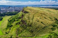 Soliga Edinburgh och gröna kullar Arkivfoton