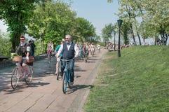 Soliga lyckliga män och kvinnor i gammal modestil som cyklar med tappning, cyklar på Retro kryssning för gatafestivalen Royaltyfria Bilder