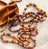 Soliga pärlor av den fasetterade agat för bärnstensfärgad spis med påsen för lädersmyckenpåse på lantlig bakgrund royaltyfri foto