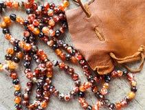 Soliga pärlor av den fasetterade agat för bärnstensfärgad spis med påsen för lädersmyckenpåse på lantlig bakgrund arkivbild