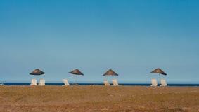 soliga paraplyer för stranddagsunbeds Royaltyfria Foton