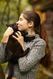 Soligt foto för sommar av slutet för katt för omfamning för tonåringflickakram upp outd royaltyfri bild