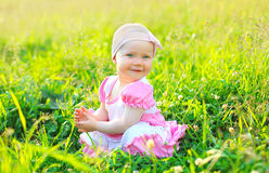 Soligt foto som ler barnsammanträde på gräset i sommar Royaltyfri Foto