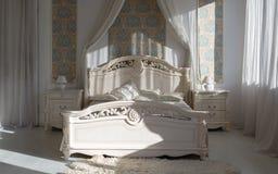 Soligt klassiskt lyxigt sovrum med vitt klassiskt möblemang royaltyfri bild