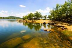 Soligt landskap med sjön Royaltyfria Foton