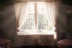 Soligt och eteriskt sovrumfönster som är öppet till det gamla mörka sovrummet royaltyfri fotografi