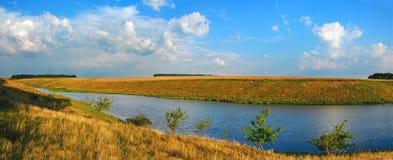 Soligt sommarlandskap med floden, gröna kullar och träd som klänger flodstranden royaltyfri foto