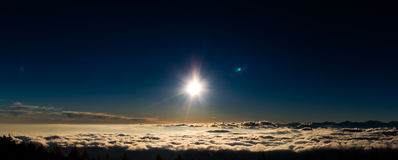 Solinställning på moln royaltyfri foto