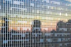 Solinställningen reflekterade i fönstren av ett affärsskyskrapakontor Arkivfoton