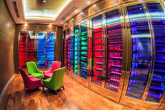 Solis Sochi Hotel wine room is performed in modern style with colorful illumination. Many wine bottles lie on shelves in wine cell Royalty Free Stock Image