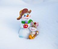 Solister av skogen kantar - snögubben och en hare Arkivfoto