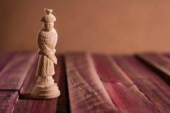 Solitair schaakstuk op een rustieke lijst met roodachtige tonen stock afbeeldingen