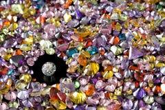 Solitaire-Diamant umgeben durch bunte Edelsteine Lizenzfreie Stockbilder