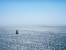 Solitaire zeilbootzeilen langs de Vreedzame Oceaan op uiterst royalty-vrije stock foto's