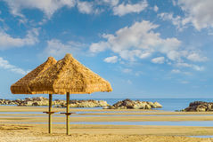 Solitaires umbrellas beach. Two solitaires umbrellas beach in the warm sun of late spring on a deserted beach still waiting for the summer and tourists Royalty Free Stock Photo