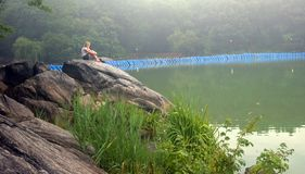 Solitary. Woman at Dusk at the Lake in Central Park, New York City Royalty Free Stock Photos