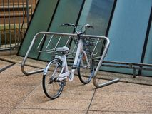 Battered Old Push Bike in Modern Stainless Steel Bike Rack. A solitary  battered old style white step through push bike or bicycle in a modern stainless steel stock image