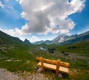 Solitary bench  on Alps valley Stock Photos