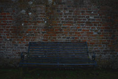 Solitary bench. A lone bench against a dark brick wall background Stock Photos