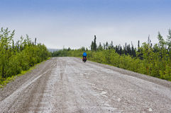 Solitary bicyclist pedals along the Dempster Highway Stock Images
