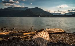 Solitary boat wood destroyed aground in a lonely beach. Lake como royalty free stock photo