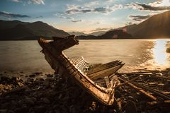 Solitary boat wood destroyed aground in a lonely beach. Lake sunset stock photo