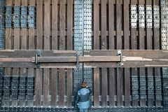 Solitary boy knocks on huge door. A small boy knocks on a huge castle door in Japan Royalty Free Stock Photos