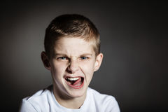 Solitary boy making faces against black background Royalty Free Stock Images