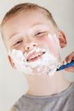Solitary boy wearing gray shirt shaving his face Stock Photos