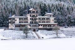 Solitary building in beautiful snowy winter forest landscape, frozen Brezova dam stock photo