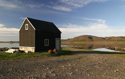 Solitary building by the lake. Lonely wooden house by the lake in the vast Iceland landscape Stock Photography