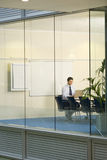 Solitary businessman working on laptop at conference table in boardroom, view through large office window Royalty Free Stock Images