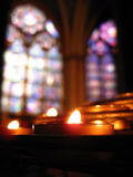 Solitary Candle & Stained Glass - Notre Dame. Solitary candle in focus at Notre Dame Cathedral, Paris with out-of-focus stained glass in the background Royalty Free Stock Photos