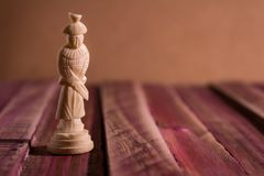 Solitary chess piece on a rustic table with reddish tones stock images
