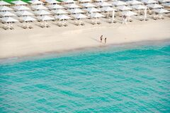 Lonely couple walking at the empty beach beside the turquoise clear water of Indian Ocean in Dubai.