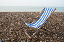 Solitary Deckchair - Grey Day. A solitary blue and white striped deckchair to right of frame, on a pebble beach with sea in the background.  Grey day Royalty Free Stock Image