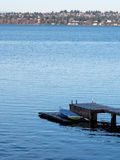 Solitary dinghy on wooden dock, copy space Stock Image