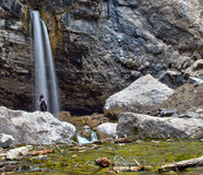 A solitary figure rests next to Spouting Rock in Glenwood Canyon, Colorado Royalty Free Stock Photo
