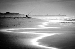 Solitary fisherman on beach at sunset. A solitary fisherman tries his luck on a sunlit beach at sunset Stock Image