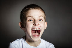 Solitary frightened boy screams in terror. Solitary frightened boy wearing white shirt in darkened room screams in terror royalty free stock photos