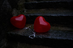 Solitary hearts. Melancholic picture of two heart-shaped baloons left on a stone stair Stock Photos