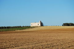 A solitary and isolated country house. A country house surrounded by a ploughed field Stock Images