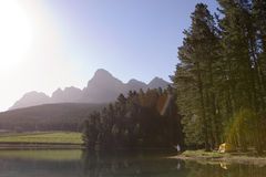 Solitary man fishing in tranquil lake on camping trip, mountain valley bathed in sunlight (lens flare) Royalty Free Stock Photography