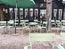 Solitary man sits among cafe tables and chairs at the outdoor cafe in the Jardin de Luxembourg, Paris, France Royalty Free Stock Image