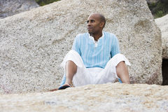Solitary man sitting beside rock on beach, thinking Stock Images