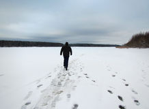 Solitary man on snowy frozen river. Solitary man walking on snowy frozen river in Russia royalty free stock photos