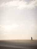 Solitary man walking through sand dunes Stock Photography