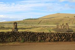 Solitary Moai near the stone fence and the famous 15 Moai on the platform at Ahu Tongariki, Easter Island. Archaeological site, UNESCO World Heritage royalty free stock photos